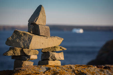inukshuk: Pile of stones and rocks forming an Inukshuk landmark along the Newfoundland Coast on the Atlantic Ocean.