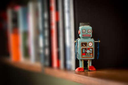 Retro tin toy robot standing on a wooden bookshelf Banco de Imagens