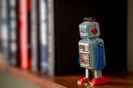 tin robot: Retro tin toy robot standing on a wooden bookshelf Stock Photo
