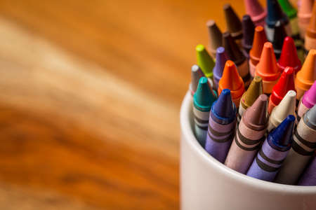 Crayons in a white mug sitting on a wooden desk.
