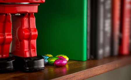 Foil wrapped easter chocolate hidden on wooden book shelf