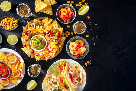 Mexican food, various dishes, shot from the top on a black background with copy space. Nachos, tacos, tequila
