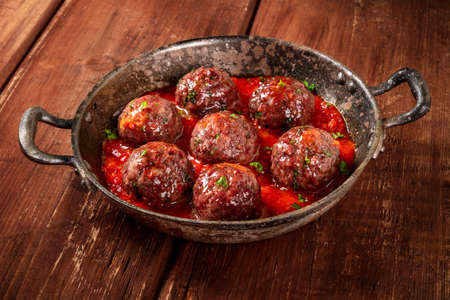 Meatballs with tomato sauce, a close-up in a pan on a dark rustic wooden background