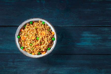Instant noodles bowl on a dark blue wooden background, shot from above with copy space