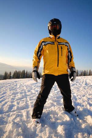 black ski pants: Skier dressing yellow coat in a black helmet
