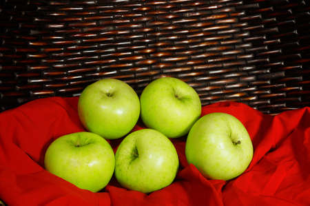 green apples: Vintage look of Green apples on red fabric with brown basket in background