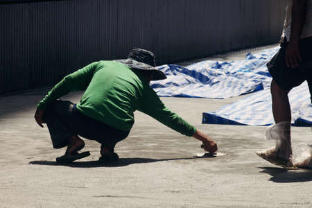 concrete surface finishing: male laborer worker smoothing the cement floor with Concrete Trowel