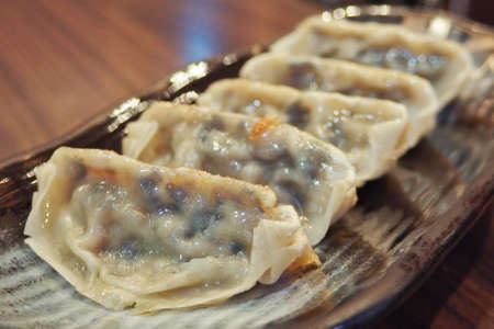 Pan-frying Dumplings dim sum arrange on long shape brown plate Фото со стока
