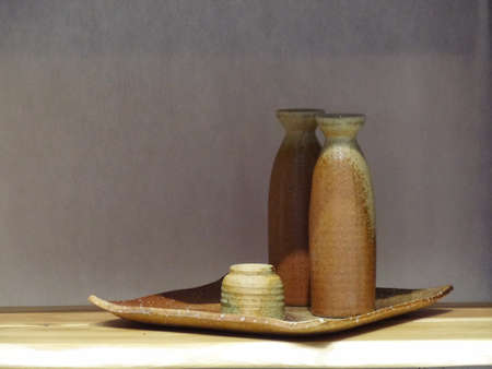 Japanese green and brown sake ceramic sets on square tray with shadow passing on top