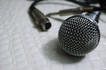 silver Grille microphone with XLR cable on white leather SELECTIVE FOCUS Zdjęcie Seryjne