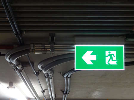 Green bright emergency fire exit with arrow show direction against metal electric wire pipe