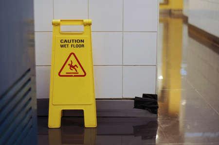 Yellow Caution wet floor cleaning in progress sign in front of toilet