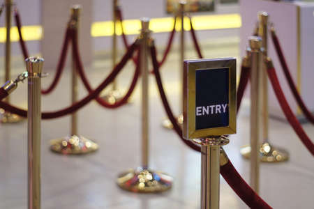 Entry / Exit sign against Rope Barrier Stanchion Queue Rope Barrier Posts Stands Crowd Control Stock Photo