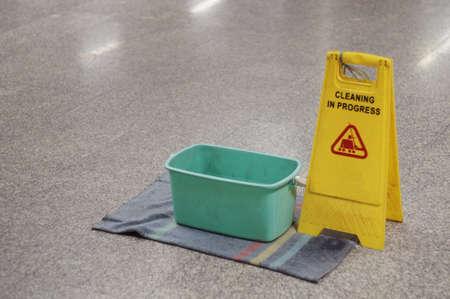 Yellow Caution wet floor cleaning in progress sign on wet floor with green bucket