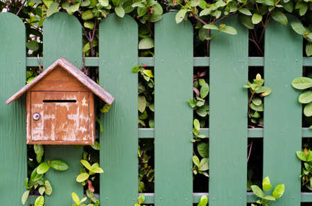 Old mailbox with green fence
