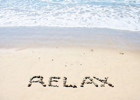 Relax written in sand at beach photo