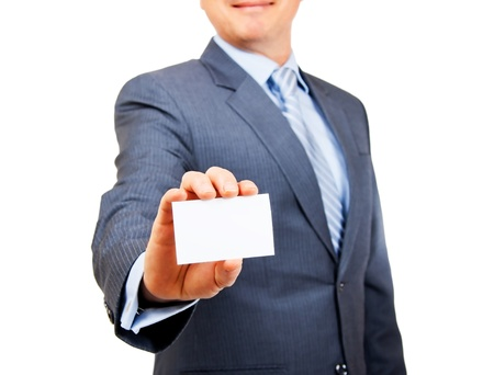 Business person in suit holding out blank white copy space card on isolated background  Focus on card  photo