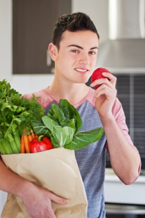 Handsome young man holding a bag of organic groceries eating a red apple Stock Photo