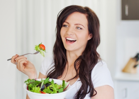 Attractive young woman eating a healthy salad