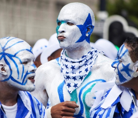 Men in carnival with painted silver and blue stars and stripes