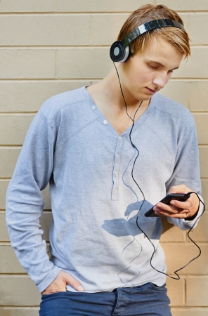 Young male scrolling through song list with sun highlighting mp3 player