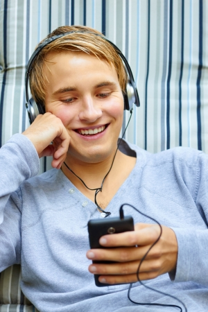 Good looking young male checking out song list on phone