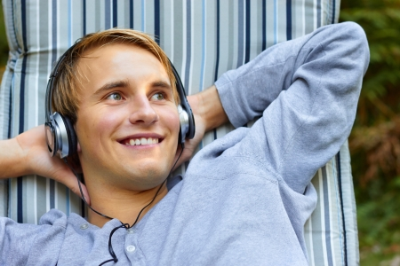 Young good looking male relaxing and listening to music with headphones