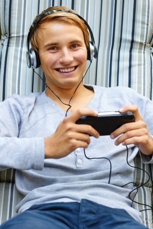 chilling out: Young male chilling out to music and playing hand-held game