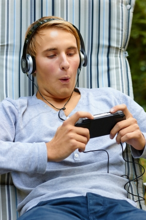 Young male having fun on game console Stock Photo