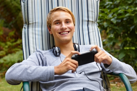 Young male relaxing in lounge outdoors with a game console and headphones