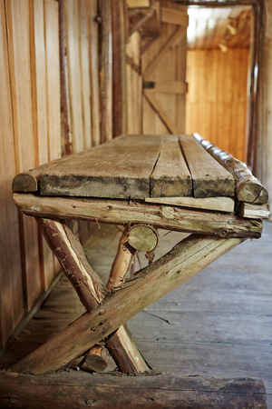 Hand made wooden bench inside old wooden cabin