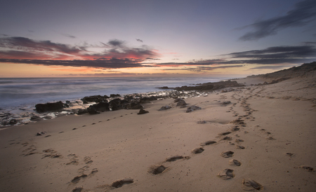 Footprints in the sand on Mornington Peninsula coastline. Stock Photo