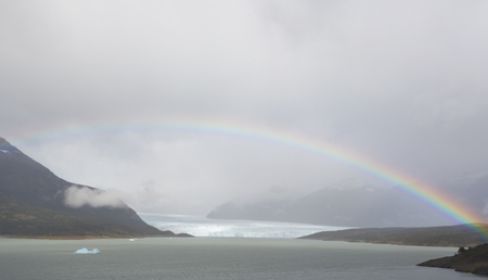 A rainbow rises over the Perito Moreno Glacier in Argentina on a haggy and hazy morning. Stock Photo
