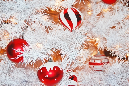 white winter: red and white christmas ornaments hanging from a frosted white christmas tree Stock Photo