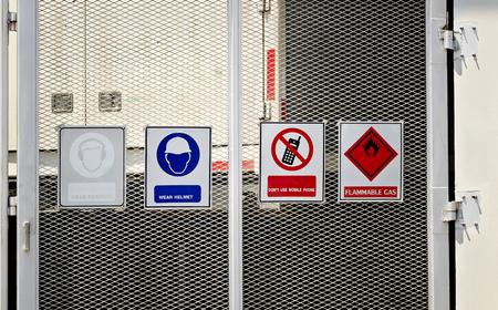 se�ales de seguridad: Grupo de los signos de advertencia en la puerta Foto de archivo