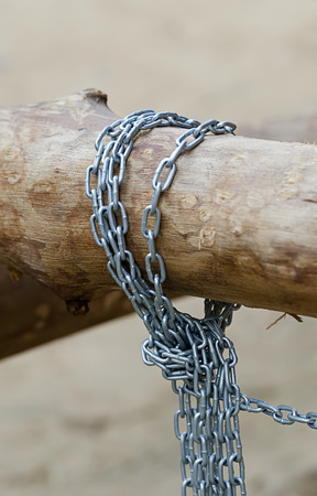 shallow: Chain tied around dry wood,shallow depth of field.