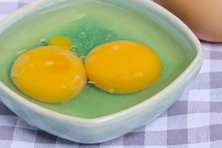 yolks: Twin eggs,two yolks in the bowl.