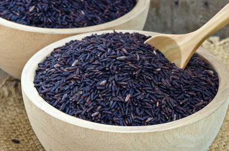 Closeup of raw purple Riceberry rice in wooden blow, it is a crossbred between Thai Hom Nil (black jasmine rice) and white Jasmine rice,Rice for health.Shallow DOF.