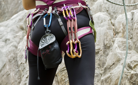 safety harness: Young female rock climber wearing safety harness with climbing tools,preparation for the climb. Stock Photo