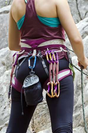 Young female rock climber wearing safety harness with climbing tools,preparation for the climb
