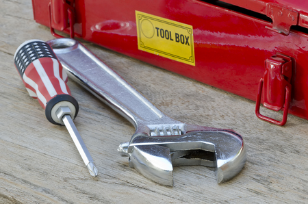 screw driver: monkey wrench and screw driver next to red tool box on wooden background.