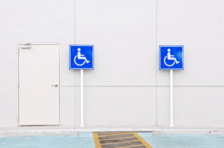 disabled parking sign: Disabled person parking sign near the wall. Stock Photo