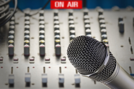 Microphone in sound studio with sound dashboard background.