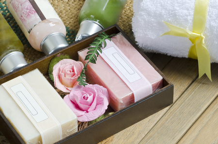 Pink and white natural soap spa with white towel on wooden background.