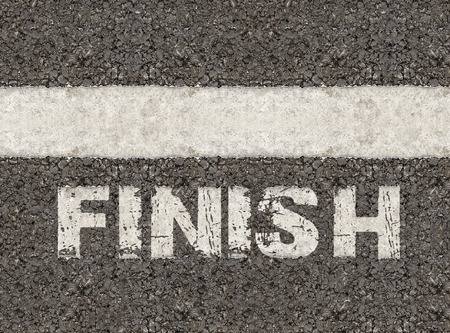 The white line on an asphalt road with a white print of the word Finish for the concept of accomplishment. 免版税图像