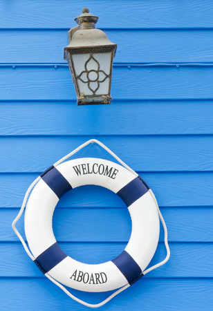 aboard: White and blue Life buoy with welcome aboard sign and old lamp on blue wall