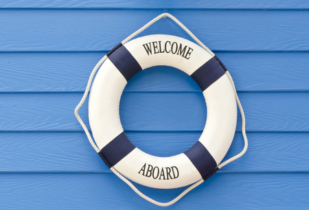 White and blue Life buoy with welcome aboard sign on blue wall Stock Photo