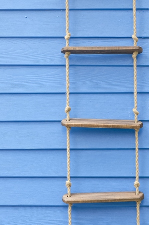 rope ladder: Rope ladder on the blue wall for background.