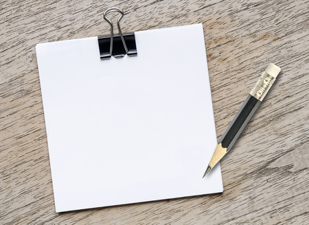 write a letter: Blank note with black pencil on wooden background. Stock Photo