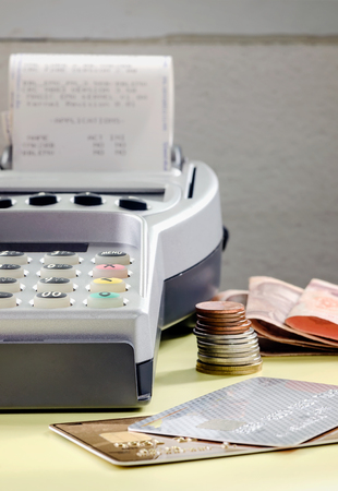 cash slips: Credit card reader with slip in close up view. Stock Photo